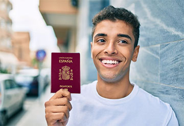 Young latin man smiling happy holding united states passport leaning on the wall at the city.