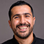 Studio shot of bearded Persian businessman wearing black shirt against gray background horizontal shot